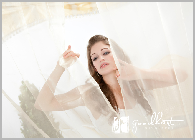 beautiful woman looking out from curtains