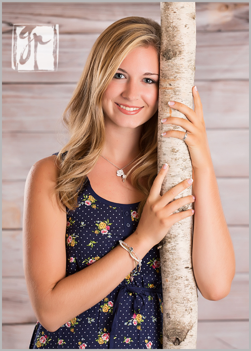 high school senior leaning against a tree