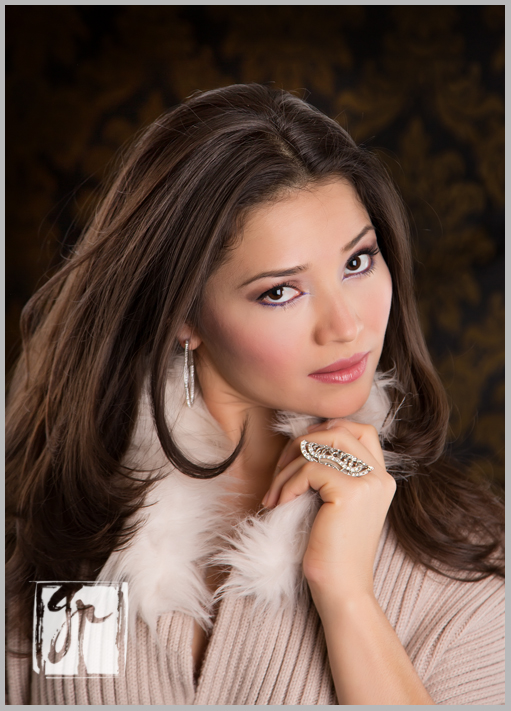 Glamorous brunette holds fur collar and wears silver ring