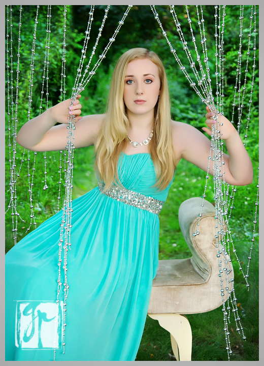 Gorgeous high school senior wearing prom dress peeking through a beaded curtain
