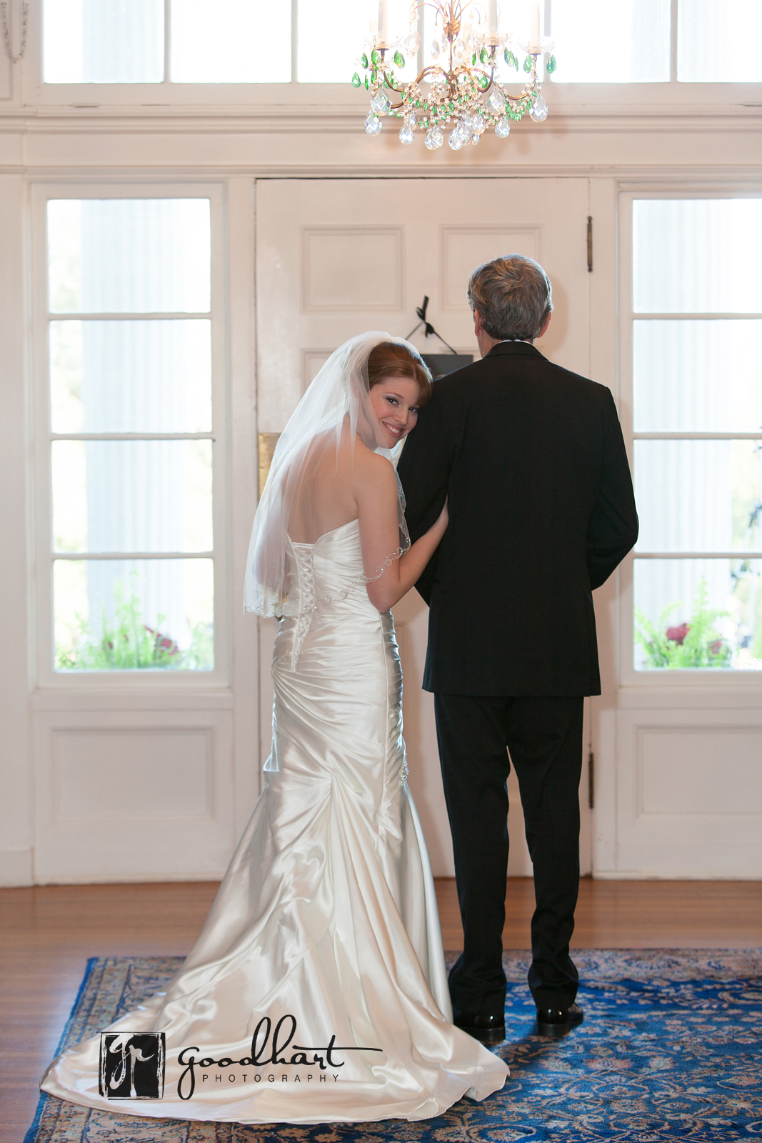 Bride peeks over fathers shoulder