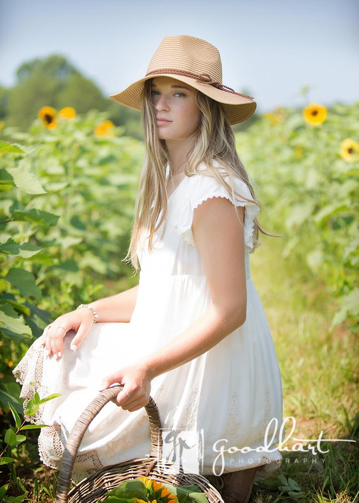 girl kneeling in sunflower fields